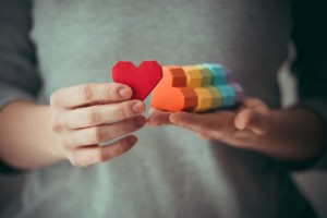 35559901 - hands holding rainbow paper hearts